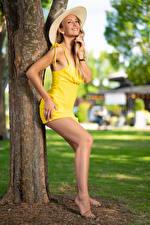 Фото Позирует Платья Шляпы Ног Ноги Улыбка Ствол дерева Девушки