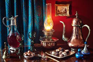 Фото Натюрморт Чайник Керосиновая лампа Вино Конфеты Кувшин Бокалы Колокольчики Еда