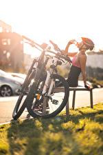 Картинка Рассветы и закаты Траве Скамейка Велосипед Шлема Сидя Пьет Релакс молодая женщина