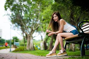 Фотографии Азиатки Скамейка Боке Шатенки Сидит Рука Ног девушка