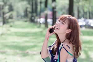 Обои Азиатки Размытый фон Шатенки Смех Руки Телефона молодые женщины