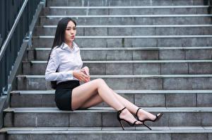 Картинка Азиаты Брюнеток Лестница Сидящие Ноги Юбка Блузка молодая женщина