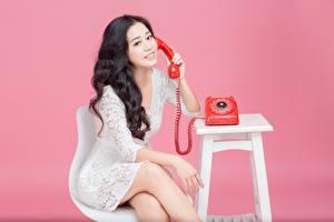 Фотография Азиаты Розовый фон Брюнетки Телефона Сидит Улыбается Руки Платья девушка