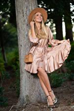 Фотографии Olga Clevenger Фотомодель Блондинки Улыбка Платья Шляпы Ног Ствол дерева молодая женщина