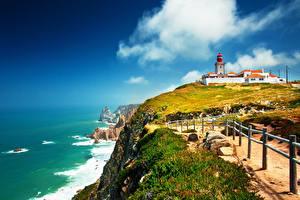 Фотография Португалия Побережье Камни Маяк Трава Забором Cape Rock, Cabo da Roca Lighthouse Природа