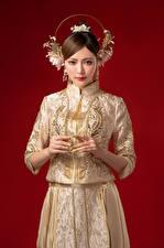 Фотография Азиаты Украшения Платья Смотрит Красный фон Руки молодые женщины