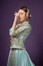 Картинка Азиаты Украшения Позирует Платье Руки Смотрят Цветной фон Девушки