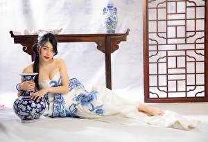 Фотография Азиаты Лежа Платья Ваза Смотрит молодая женщина