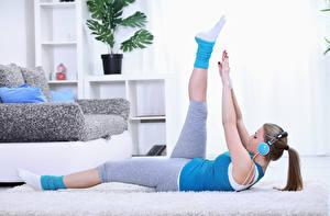Картинка Фитнес Русых В наушниках Лежат Рука Ноги Униформе Тренировка девушка Спорт