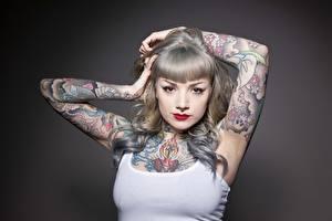 Обои Сером фоне Смотрят Руки Татуировки Макияж Пирсингом молодая женщина