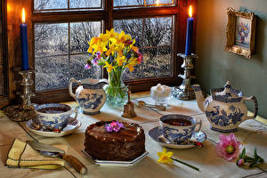 Фото Натюрморт Торты Чай Нарциссы Свечи Морозник Ножик Чашка Ваза Еда