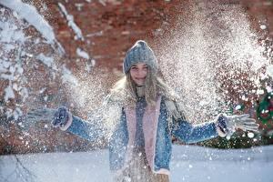 Фотографии Зима Снег Улыбается В шапке Куртка Рука Перчатки молодая женщина