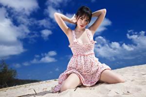 Картинки Азиатка Песке Сидящие Платья Взгляд Позирует молодая женщина