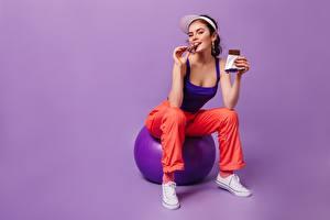 Обои для рабочего стола Шоколад Шоколадная плитка Улыбка Мячик Сидит Майки Кепка Смотрят Цветной фон девушка