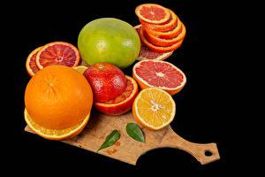Обои Цитрусовые Апельсин Грейпфрут Лайм На черном фоне Разделочной доске Еда