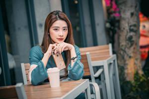 Фотографии Азиаты Apple Рука Смартфон Взгляд Боке Стола Шатенка Девушки