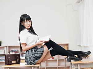 Фото Азиатки Брюнеток Сидит Униформа Школьница Ног Гольфы Взгляд Красивая молодая женщина