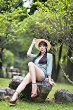 Фотография Азиаты Камень Брюнетка Сидит Ног Рубашка Шорты Шляпа Размытый фон молодые женщины