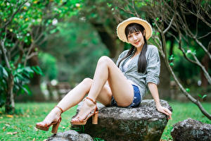 Картинка Азиатка Камень Сидит Ног Шорт Шляпе Рубашки Брюнетки Взгляд Поза девушка