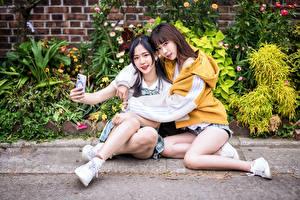 Фото Азиаты Двое Сидя Обнимаются Селфи молодые женщины