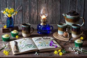 Фотография Натюрморт Нарциссы Галантус Керосиновая лампа Пирожное Стены Доски Вазе Книга Кружка Пища