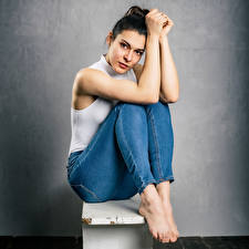 Картинка Брюнеток Сидящие Позирует Джинсов Майке Смотрят Angelina молодая женщина