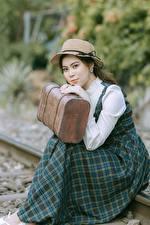 Картинки Азиатки Размытый фон Рельсы Платья Шляпы Чемоданы Сидя молодые женщины