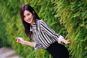 Фотографии Азиаты Взгляд Улыбка Брюнетки Кустов Рука молодая женщина
