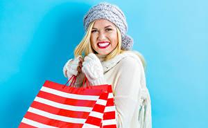 Фотография Цветной фон Блондинка Смотрят Шапки Улыбка Красными губами Перчатки Бумажный пакет Девушки