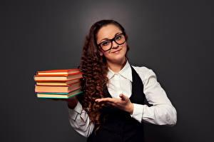 Фотография Кудрявые Серый фон Шатенка Улыбка Книга Руки Очки Смотрит молодая женщина