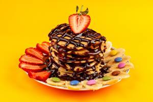 Фотография Блины Клубника Драже Шоколад Бананы Тарелка Цветной фон Продукты питания