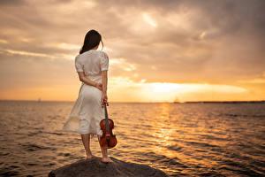Картинки Море Рассвет и закат Камень Скрипка Платье Yaroslav Kotov молодая женщина Природа