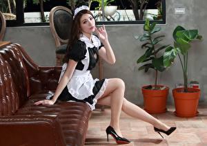 Картинки Азиаты Диван Сидящие Горничная Униформе Ног Смотрит Девушки