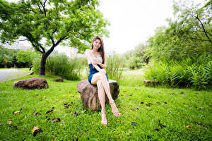 Обои Азиатки Камень Сидит Ног Улыбка Взгляд молодая женщина