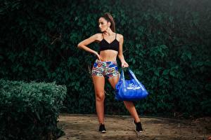 Фото Сумка Кустов Шатенки Позирует Шортах Рука Ноги молодая женщина