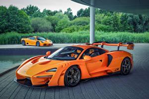 Фотографии Макларен Оранжевые Металлик Вдвоем McLaren F1, McLaren Senna LM Автомобили