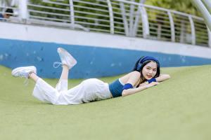 Фото Азиаты Брюнеток Лежит В наушниках Ног Кроссовках молодые женщины