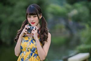 Картинки Азиаты Фотокамера Рука Смотрят Размытый фон девушка