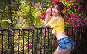 Фотографии Азиаты Ограда Шатенки Взгляд Улыбка Шорты девушка