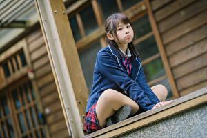 Фотография Азиаты Позирует Сидит Униформа Школьница Смотрит молодые женщины