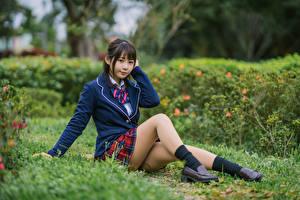 Фотографии Азиатка Позирует Сидящие Униформа Школьницы Ног Смотрят девушка