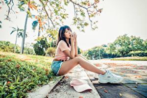 Фото Азиатки Сидит Ноги Кроссовки Рука Взгляд молодые женщины