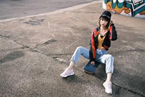 Обои Азиаты Скейтборд Сидит Джинсов В шапке Кроссовках Взгляд молодые женщины