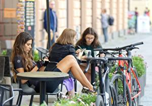 Фотографии Размытый фон Шатенка Стола Сидя Кафе Велосипеде Девушки