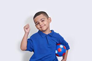 Обои для рабочего стола Серый фон Мальчишка Мяч Улыбка Рука Смотрит ребёнок